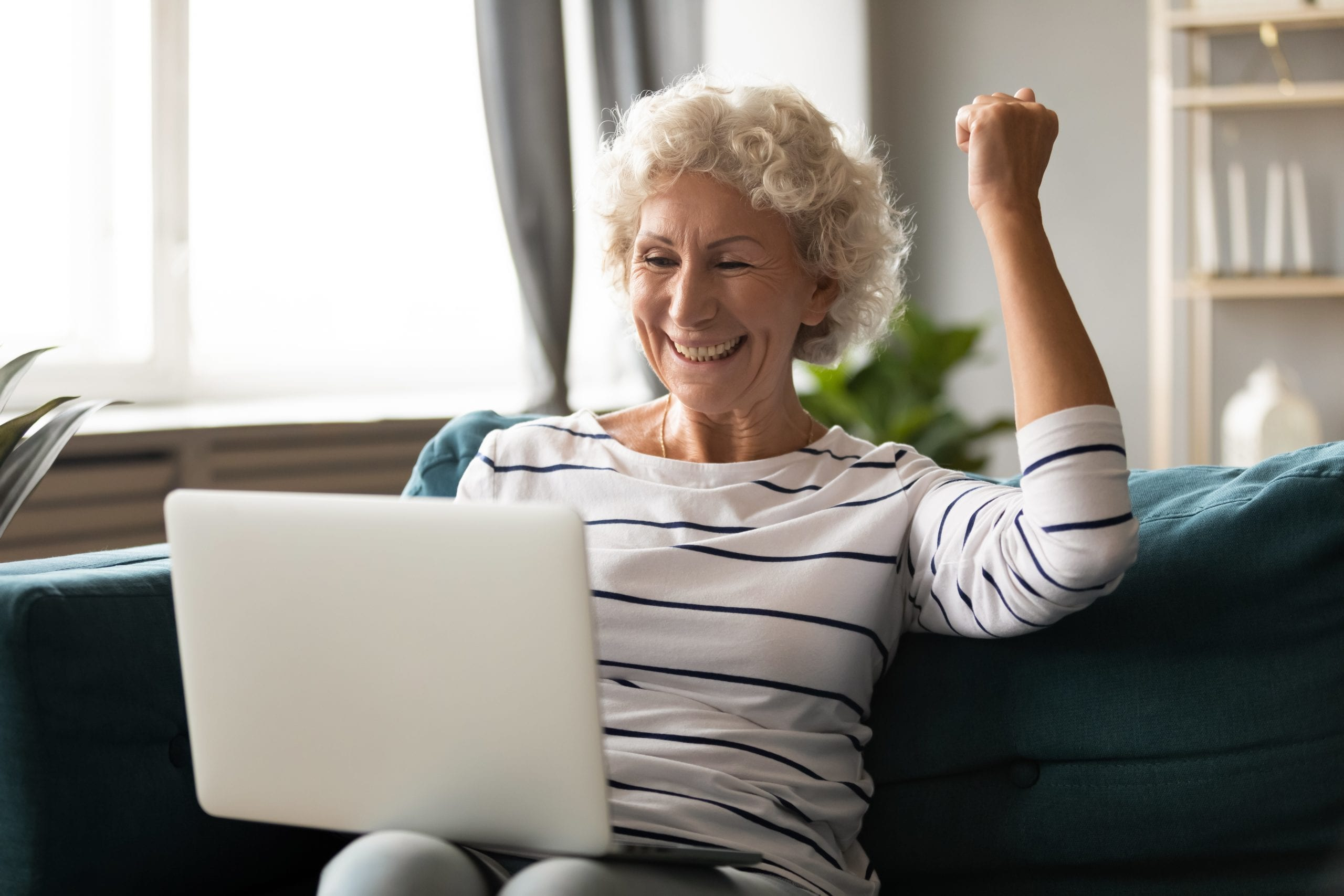 Excited mature woman relax with laptop read amazing news